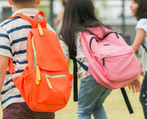 Niños cargan unas pesadas mochilas